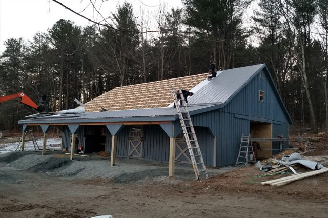 Workers add a new metal roof in MA