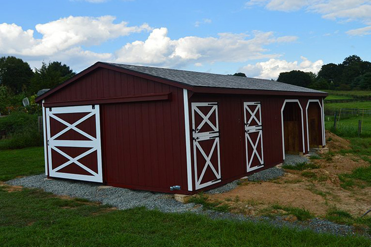 Small red horse barn with white trim