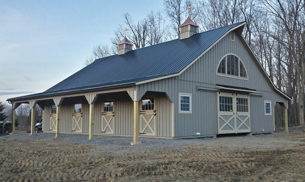Light gray horse barn with white trim