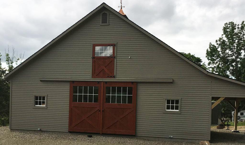 Green barn with natural wood doors