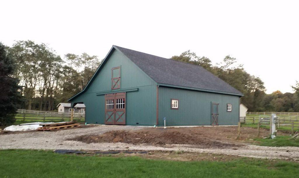 Dark green horse barn with brown door