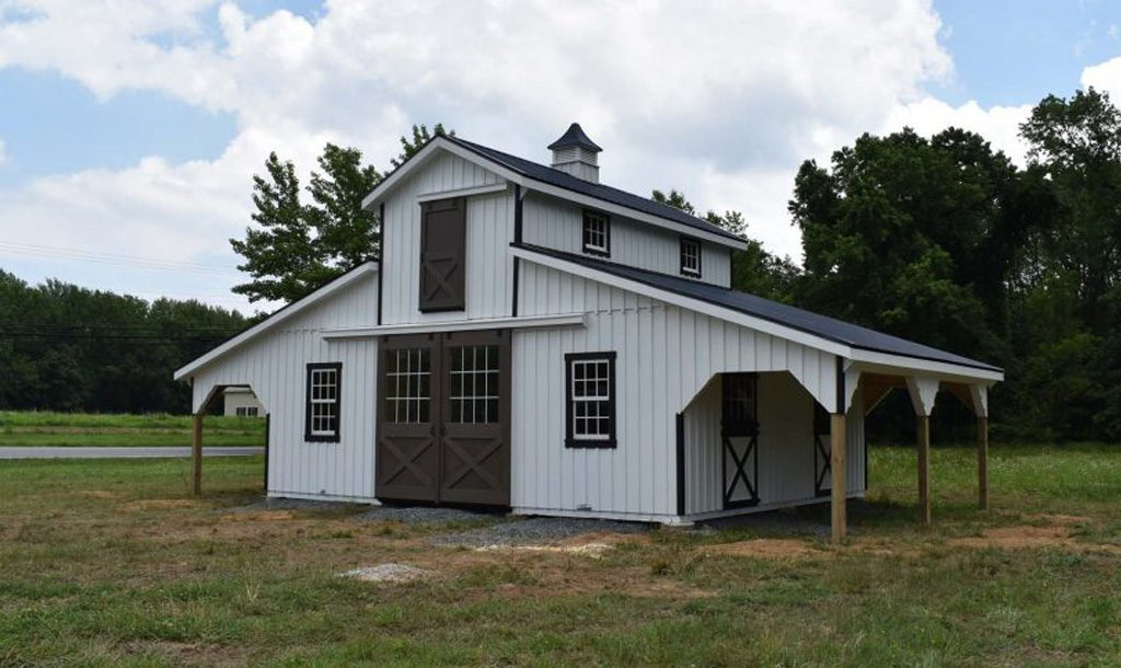 Two story horse barn white with black trim
