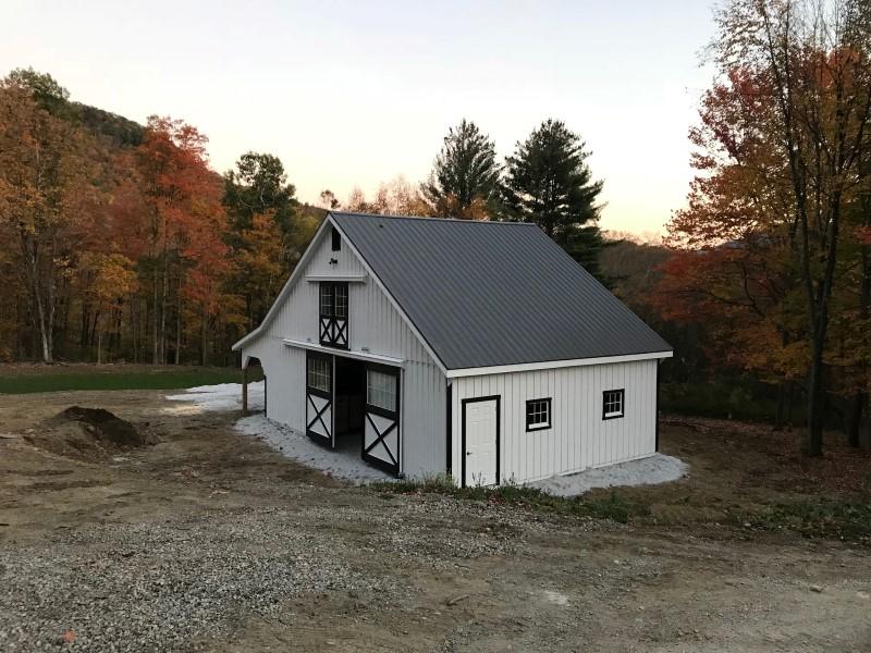 White horse barn with dark trim