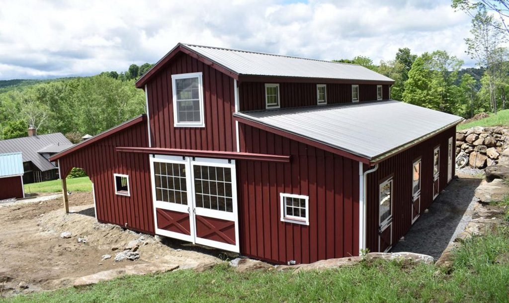 Red two story horse barn with white trim