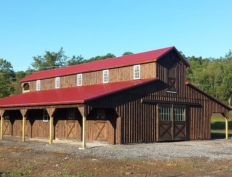 Brown horse barn with red roof