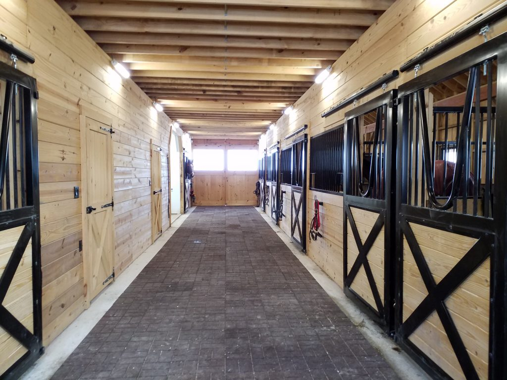 Horse stalls inside large custom horse barn