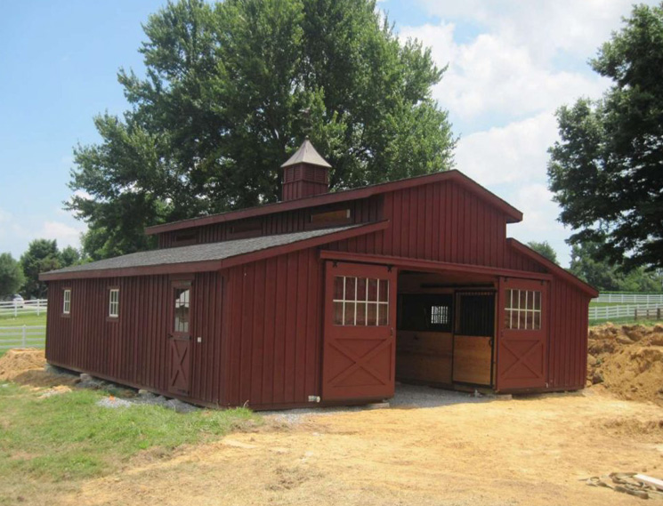 Red single story center aisle custom barn
